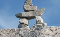 pile of rocks in shape of inuksuk on larger rock